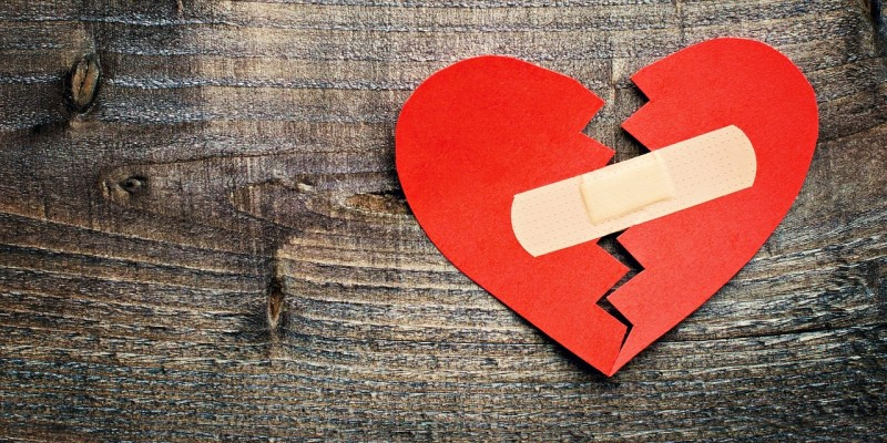 broken heart with bandage on wood background